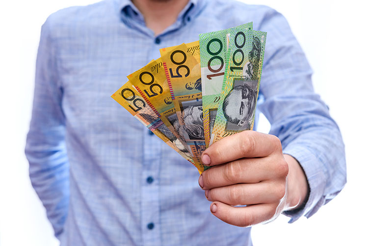 tax return in mans hand with australian money
